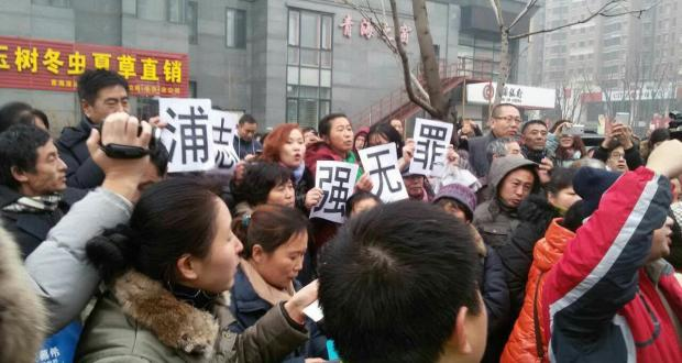 """Supporters of Pu Zhiqiang protesting outside court during his trial on Monday, December 14, 2015. Placards: """"Pu Zhiqiang not guilty."""""""