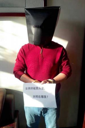 "Online performance art campaign initiated by women human rights defenders to protest the thug-like treatment of lawyer Wang Shengsheng. Placards read: ""Women lawyers in black hoods, where is the light?"""