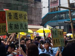 """Signs: """"Universal Suffrage in Chief Executive Election Helps People's Welfare"""" (left) and """"If Not Passed Now, 10 More Years of Waiting,"""" at the """"The Citizens Against Pseudo-Universal Suffrage"""" march, Hong Kong, June 14, 2015. HRIC photo."""