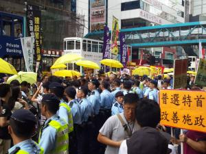 "Police separate democracy protesters from supporters of electoral reform package, at the ""The Citizens Against Pseudo-Universal Suffrage"" march, Hong Kong, June 14, 2015. HRIC photo."
