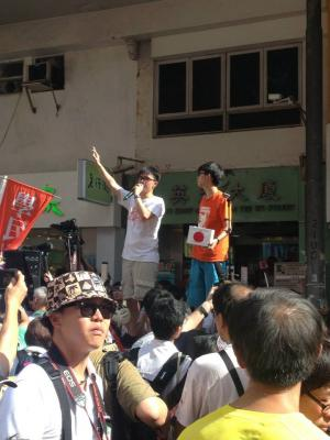 Joshua Wong and another Scholarism member talk to participants in the democracy march organized by Civil Human Rights Front, from Victoria Park to Tim Mei Avenue, Hong Kong, July 1, 2015. HRIC photo.