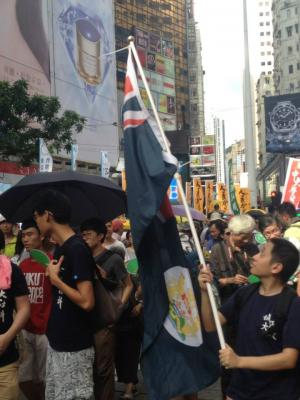 A marcher waves the colonial-era Hong Kong flag during the democracy march organized by Civil Human Rights Front, Hong Kong, July 1, 2015. HRIC photo.