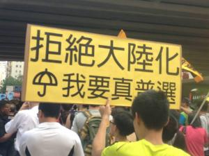 "Participant holds sign that reads: ""Reject Mainlandization, I Want Genuine Universal Suffrage,"" during the democracy march organized by Civil Human Rights Front, Hong Kong, July 1, 2015. HRIC photo."