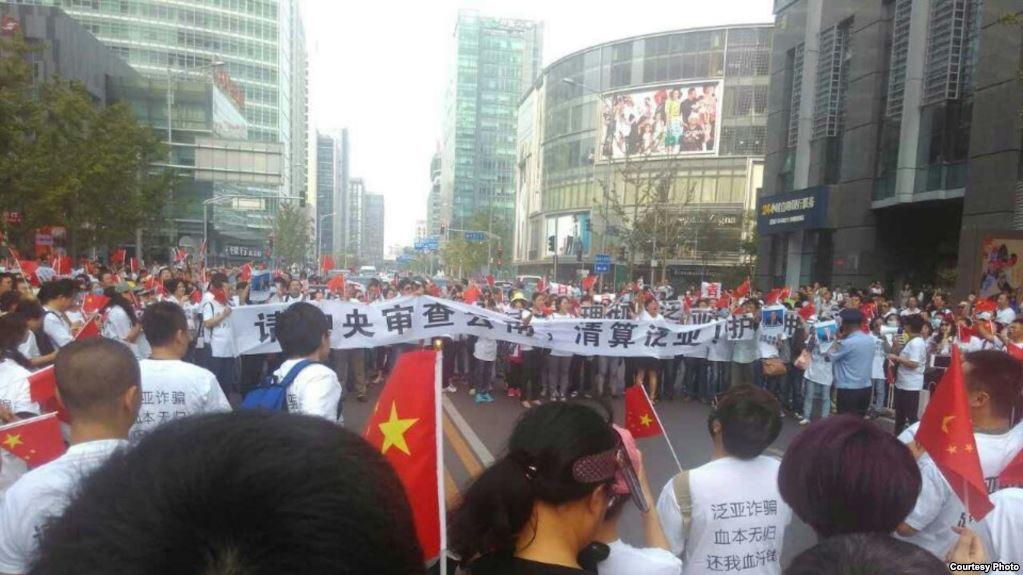 """千余人围堵在北京市金融街的中国证监会门口,他们统一身穿背后写有""""泛亚诈骗,血本无归,还我血汗钱""""的白体恤,手举""""请中央审查云南,清算泛亚""""的标语。"""