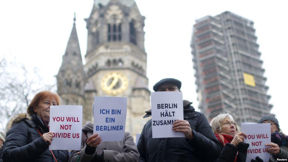 """柏林人和难民们在大教堂前并肩演唱""""我们是世界""""(2016年12月21日)"""
